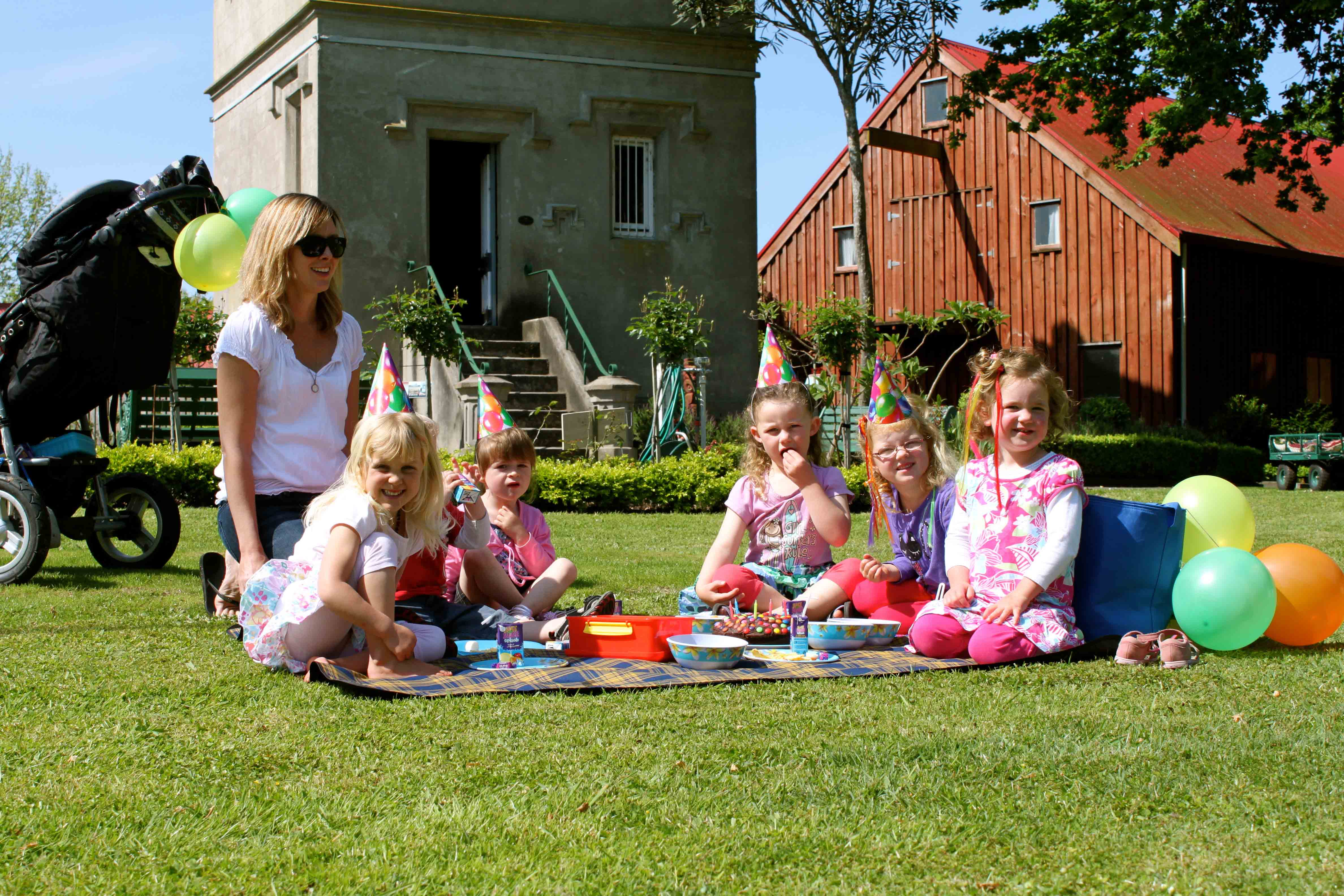 Mum with kids sitting on grass having a picnic